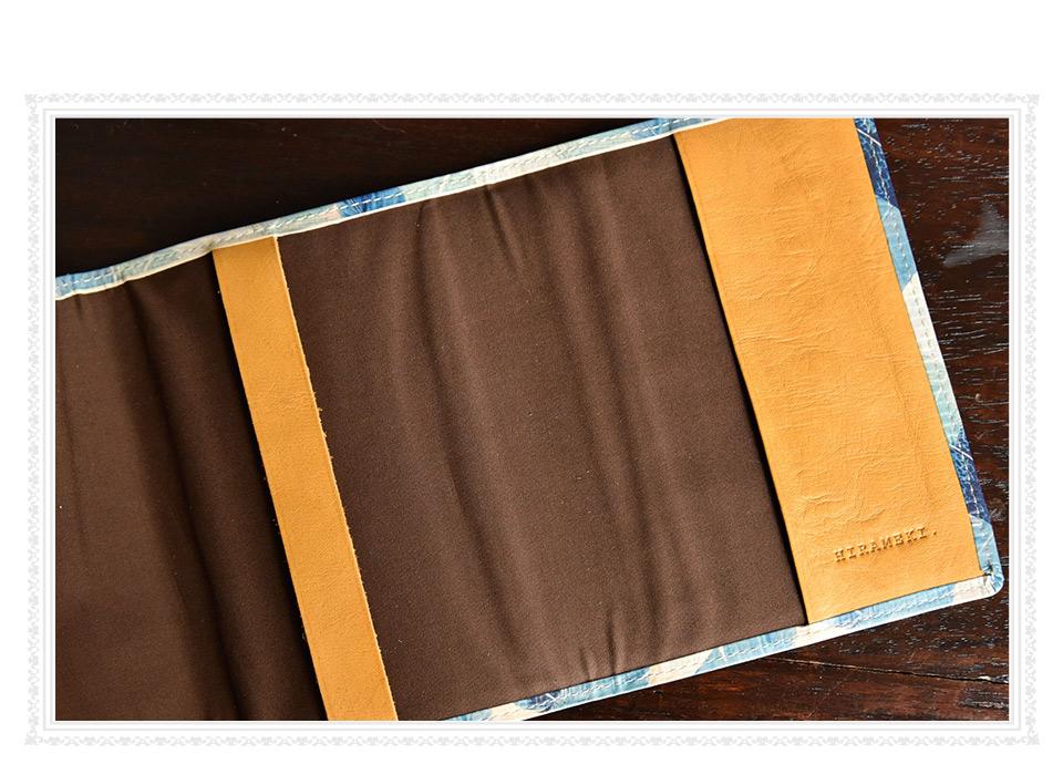 ブックカバーの内側、ブラウンの綿生地と、右側の革の下部に入ったHIRAMEKI.のブランドロゴの刻印イメージ
